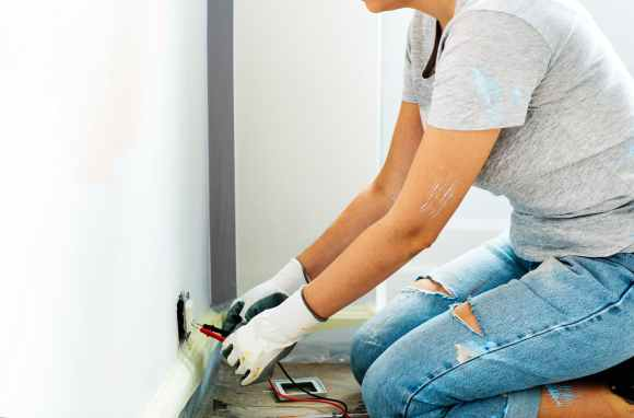 person holding multimeter beside white painted wall