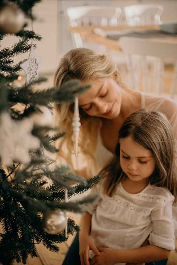 woman and girl standing beside christmas tree