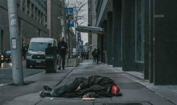 photo of man laying on sidewalk
