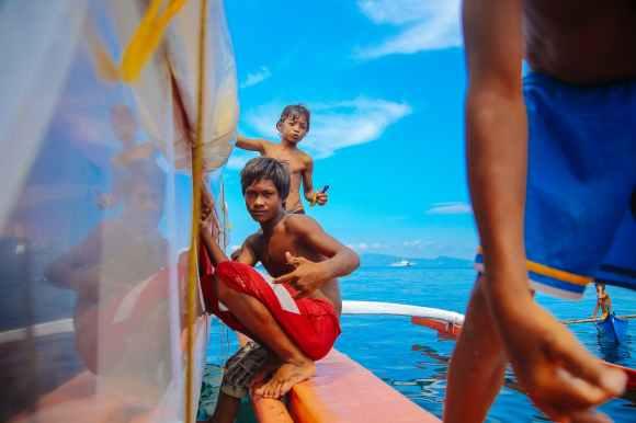 teenage boys sitting on edge of boat